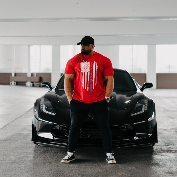 Bodybuilder Fouad Abiad standing in front of corvette wearing Patriot t-shirt