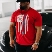 Bodybuilder Fouad Abiad standing to the side of corvette wearing Patriot t-shirt