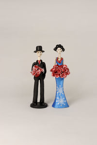 Hand-made clay figurine, Cynthia is wearing a curve-skimming blue dress with silver details on her dress.She is holding a red rose bouquet. Her date, Diego is also holding a red rose bouquet that matches Cynthia's bouquet. All our Catrinas are made in Mexico and shipped worldwide. Add a classy touch of Mexican culture to your home.