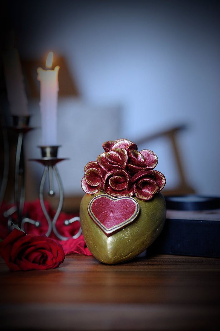 Hand-made clay heart, painted in gold. For decoration, the artist added a heart and a bouquet of red roses with splashes of gold. This beautiful Valentine's Day heart can also be hung on a wall. All our Catrinas and hearts are made in Mexico and we ship worldwide. Add a classy touch of Mexican art to your home.
