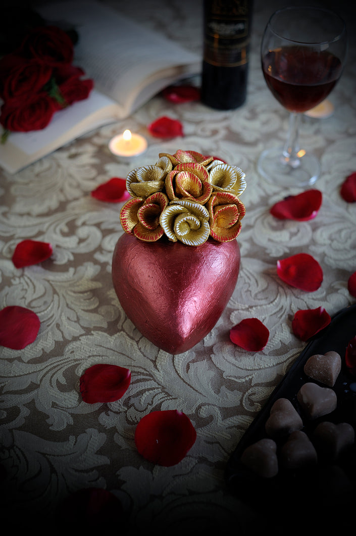 Hand-made clay heart, painted in metallic red giving the illusion of a heart shaped chocolate wrapped in red foil. On top it is beautifully decorated with a bouquet of roses painted in metallic gold. This stunning heart decoration can also be hung on a wall. All our catrinas and hearts are made in Mexico and we ship worldwide. Add a classy touch of Mexican art to your home.