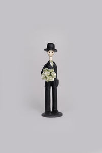Hand-made clay figurine, Catrin Martin in gold is a small but fancy guy, he is wearing a tux with a gold tie and he is holding a gold rose bouquet. He is the perfect partner for any small Catrina. All our Catrines and Catrinas are made in Mexico and we ship worldwide. Add a classy touch of Mexican art to your home.