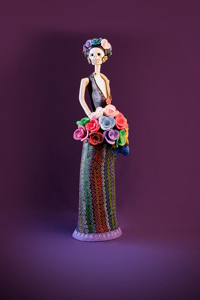 Hand-made clay figurine, Alejandra is wearing a plunging neckline with a dotted pattern A-line skirt. She has a colorful bouquet of roses and she is also wearing a roses headpiece. Add a touch of Mexican art to your home. We ship worldwide