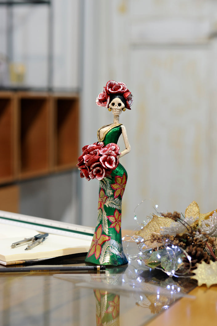 Catrina Cynthia Christmas Green is a hand-made clay figurine, Cynthia is wearing a curve-skimming green dress with gold poinsettias on her dress.She is holding a red rose bouquet. All our Catrinas are made in Mexico and shipped worldwide. Add a classy touch of Mexican culture to your home.