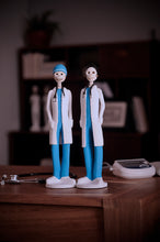 Load image into Gallery viewer, Hand-made clay figurines, Dr.Hope and Dr.Angel are both wearing blue scrubs and white coats, the Earth's Angels collection was made to honor front-line workers during the covid-19 pandemic. All our Catrines and Catrinas are made in Mexico, we ship worldwide. Add a classy touch of Mexican art to your home or office.