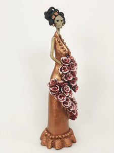 Hand-made clay figurine, Catrina Carolina in Bronze is a stunning Catrina wearing a copper dress with detailing at the bottom. For added style she is holding a wrapped bouquet of beautiful roses. All our Catrinas are made in Mexico and we ship worldwide. Add a classy touch of Mexican culture to your home.