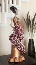 Load image into Gallery viewer, Hand-made clay figurine, Catrina Carolina in Bronze is a stunning Catrina wearing a copper dress with detailing at the bottom. For added style she is holding a wrapped bouquet of beautiful roses. All our Catrinas are made in Mexico and we ship worldwide. Add a classy touch of Mexican culture to your home.