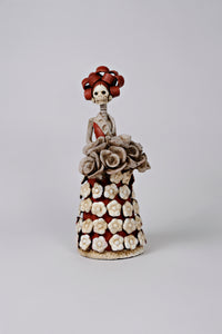 Hand-made clay figurine, the dress and hair are painted in rust and some details on the dress like the flowers on the dress and bouquet are painted in ivory. All our Catrinas are made in Mexico and shipped worldwide. Add a classy touch of Mexican art to your home.
