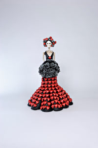 Hand-made clay figurine, Catrina Elena is wearing a black dress with sculpted red hearts placed all over her gown. She is also wearing a stunning flower bouquet of black roses with a white dotted pattern, Elena is a perfect Valentine's Day gift.  All our Catrinas are made in Mexico, we ship worldwide. Add a classy touch of Mexican art to your home.