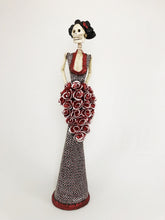 Load image into Gallery viewer, Hand-made clay figurine, Estela in burnt sienna is one of our tallest Catrinas. She is wearing a sleek trumpet style dress, with a deep neckline. Her stunning dress has a dotted flower design that makes her cascading bouquet stand-out even more. All our Catrinas are made in Mexico, we ship worldwide. Add a classy touch of Mexican art to your home or office.
