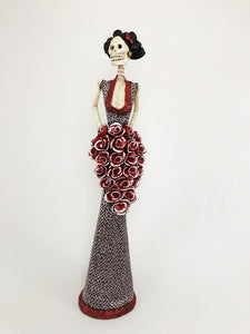 Hand-made clay figurine, Estela in burnt sienna is one of our tallest Catrinas. She is wearing a sleek trumpet style dress, with a deep neckline. Her stunning dress has a dotted flower design that makes her cascading bouquet stand-out even more. All our Catrinas are made in Mexico, we ship worldwide. Add a classy touch of Mexican art to your home or office.