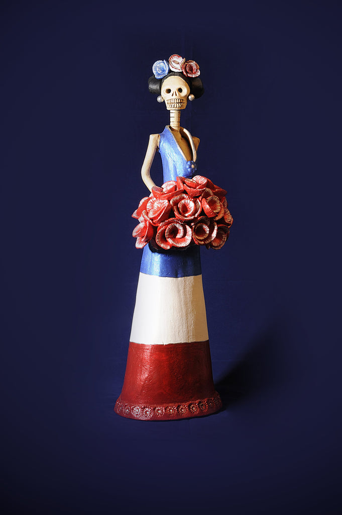 Hand-made clay figurine, Catrina Miss France is a beautiful Catrina wearing a dress that resembles France's flag. Her headpiece also has the colors of her flag, and to finish the outfit, she is holding a e rose bouquet. All our Catrinas are made in Mexico and we ship worldwide. Add a classy touch of Mexican culture to your home.
