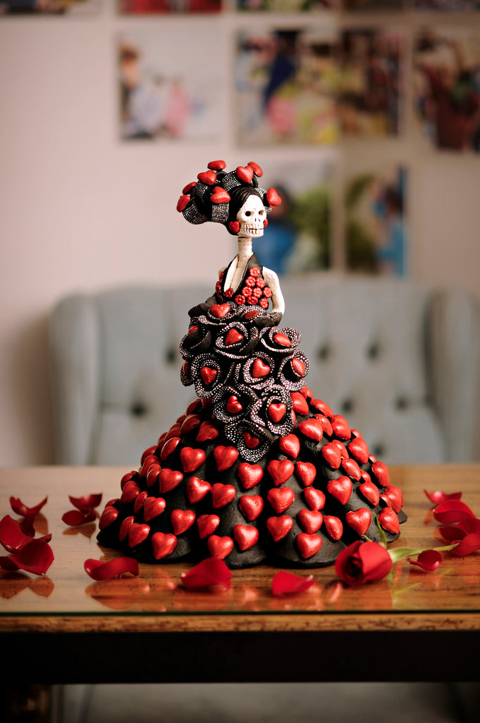 Hand-made clay figurine, Catrina Gina is part of our Valentine's Day collection. She is wearing a stunning black dress covered in hearts. Her bouquet of black roses also has red hearts to match her headpiece and her dress. All our Catrinas are made in Mexico but we ship worldwide. Add a classy touch of Mexican art to your home.