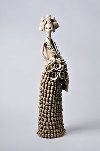 Hand-made clay figurine, Catrina Felicia is part of our Day of the Dead collection, her dress is made with little skulls and she is holding a cascading bouquet. All our Catrinas are made in Mexico, we ship worldwide. Add a dd a classy touch of Mexican culture to your home or office.