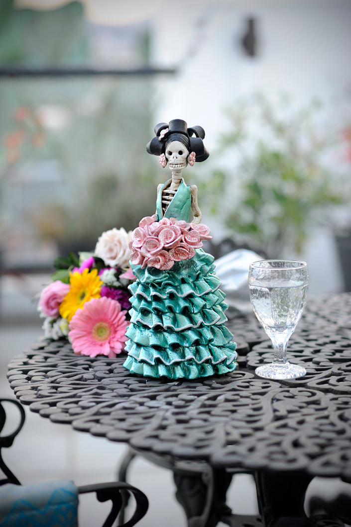 Hand-made clay figurine, wearing a turquoise ruffled dress. Berenice is holding a beautiful pink dotted rose bouquet. Add a classy touch of Mexican art to your home or office. All our Catrinas are made in Mexico. We ship worldwide.