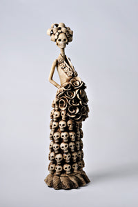 Hand-made clay figurine, Catrina Salome is wearing a dress with hand-made skulls carefully placed all over her dress. She makes a great addition to any Day of the Dead altar. All our Catrinas are made in Mexico, and we ship worldwide. Add a classy touch of Mexican culture to your home.