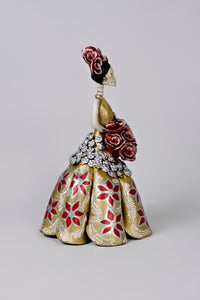 Hand-made clay figurine, made in Mexico. Shipped worldwide. Amanda in Gold is a stunning Christmas catrina, dress painted in gold, hand-painted poinsettias, small silver accent flowers under the bouquet, gorgeous red rose bouquet that compliments her headpiece.