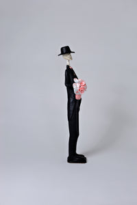 26 inch tall, hand-made clay figurine. Our male Catrin Brandon is wearing a traditional tux, with a pink waistcoat and pink bow tie that match the pink flower bouquet he is holding for his lovely bride. He is also wearing a hat to compliment his look. All our Catrinas are made in Mexico. We ship worldwide. Add a classy touch of Mexican art to your home or office!