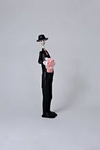 Load image into Gallery viewer, 26 inch tall, hand-made clay figurine. Our male Catrin Brandon is wearing a traditional tux, with a pink waistcoat and pink bow tie that match the pink flower bouquet he is holding for his lovely bride. He is also wearing a hat to compliment his look. All our Catrinas are made in Mexico. We ship worldwide. Add a classy touch of Mexican art to your home or office!