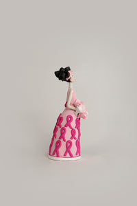 Hand-made clay figurine, Elisa is part of our Breast Cancer Awareness collection, she is wearing a baby pink dress with dark pink ribbons. She is also sporting a pink headband and a pink flower bouquet that matches her dress. All our Catrinas are made in Mexico and shipped worldwide. Add a classy touch of Mexican art to your home.