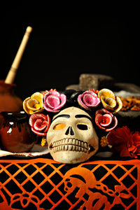Hand-made clay skull, decorated with flowers, it has an opening in the back so you can place a candle inside, decorate your Day of the Dead altar with one of these skulls. All our Catrinas and skulls are made in Mexico and shipped worldwide.