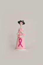 Load image into Gallery viewer, Hand-made clay figurine, Liliana is part of our Breast Cancer Awareness collection, she is wearing a baby pink dress with a matching flower bouquet and headband. Her dress has a hand-painted pink ribbon in honor of this month's significance. All our Catrinas are made in Mexico, we ship worldwide. Add a classy touch of Mexican culture to your home.