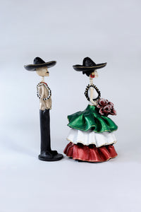 Hand-made clay figurines, Adelita is wearing a ruffled dress, the colors of her dress represent the Mexican flag. Green, white and red. She is wearing a traditional hat and bullet belt, her date Emiliano is also wearing the hat and bullet belt. This couple represents the era of the revolution in Mexico.Bring a touch if Mexican culture to your home. We ship worldwide.