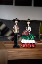 Load image into Gallery viewer, Hand-made clay figurines, Adelita is wearing a ruffled dress, the colors of her dress represent the Mexican flag. Green, white and red. She is wearing a traditional hat and bullet belt, her date Emiliano is also wearing the hat and bullet belt. This couple represents the era of the revolution in Mexico.Bring a touch if Mexican culture to your home. We ship worldwide.