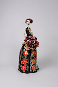Hand-made clay figurine, Catrina Fernanda is ready for the Christmas party, she is wearing a beautiful black dress, decorated with hand-painted poinsettias and small gold flowers around her bouquet of roses. She is also wearing a beautiful headpiece. Add a classy touch of Mexican art to your home or office. All our Catrinas are made in Mexico and shipped worldwide.