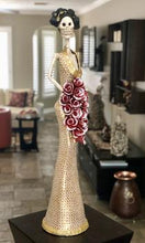 Load image into Gallery viewer, Hand-made clay figurine, Estela is one of our tallest Catrinas. She is wearing a sleek trumpet style dress, with a deep neckline. Her stunning dress has a dotted flower design that makes her cascading bouquet stand-out even more. All our Catrinas are made in Mexico, we ship worldwide. Add a classy touch of Mexican art to your home or office.