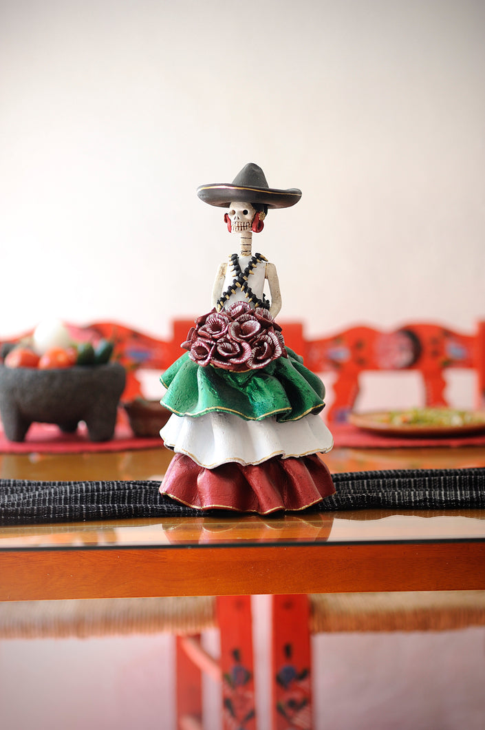 Hand-made clay figurine, Adelita is wearing a ruffled dress, the colors of her dress represent the Mexican flag. Green, white and red. She is wearing a traditional hat and bullet belt, all symbols of the Revolution era.Bring a touch if Mexican culture to your home. We ship worldwide.
