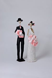 Hand-made clay figurines, Daniela and Brandon are a Catrina couple who are celebrating their recent marriage. She is wearing a beautiful white dress covered in little white rosebuds, while her husband is wearing a classic tux with a pink cummerbund that matches the rose bouquets they are both holding. All our Catrinas are made in Mexico and we ship worldwide. Add a touch of classy Mexican art to your home.
