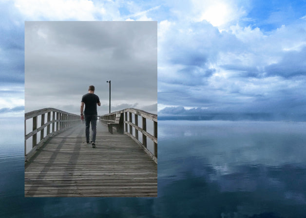 A cloudy sky reflected on water with a photo of a man walking down a foggy pier. Photos by Lindsay Windham