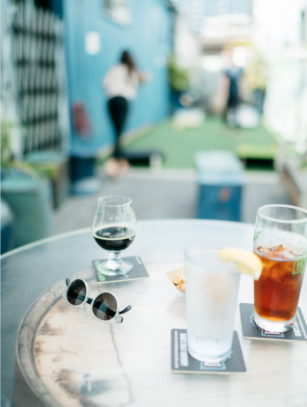 A pair of Cooper MagLock sunglasses sit on a table with pints of cold beers while people play games in the background