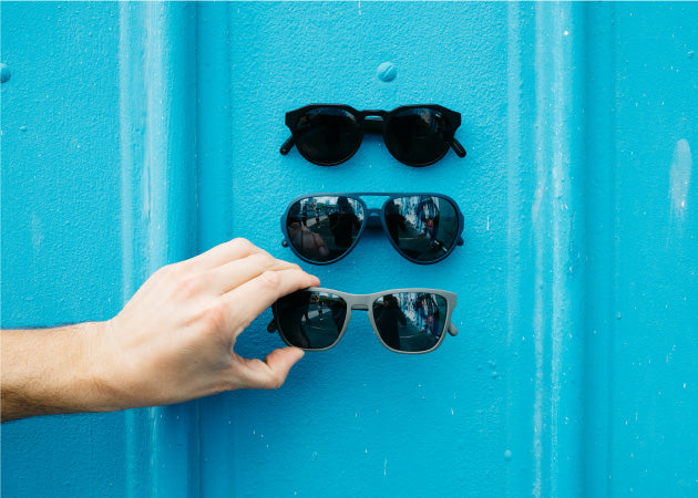 Distil Union MagLock Sunglasses are held in place on a blue metal wall thanks to hidden magnets in the frames