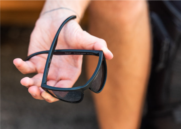 A flexible pair of Folly MagLock Sunglasses being bent in someone's hands