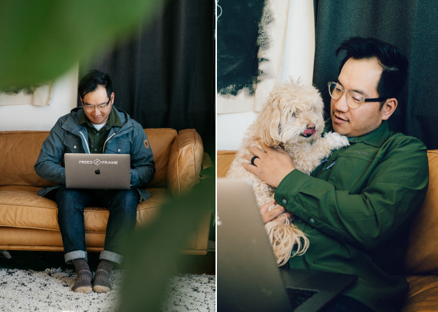 A man works on his laptop, accompanied by a dog