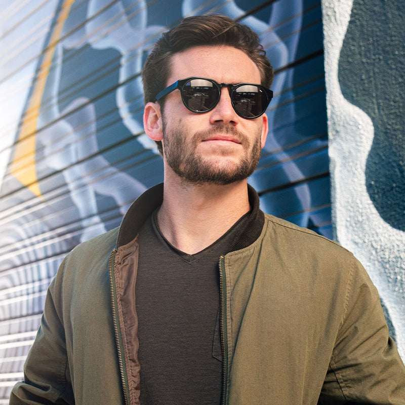 bearded man wearing distil cooper sunglasses, green bomber jacket