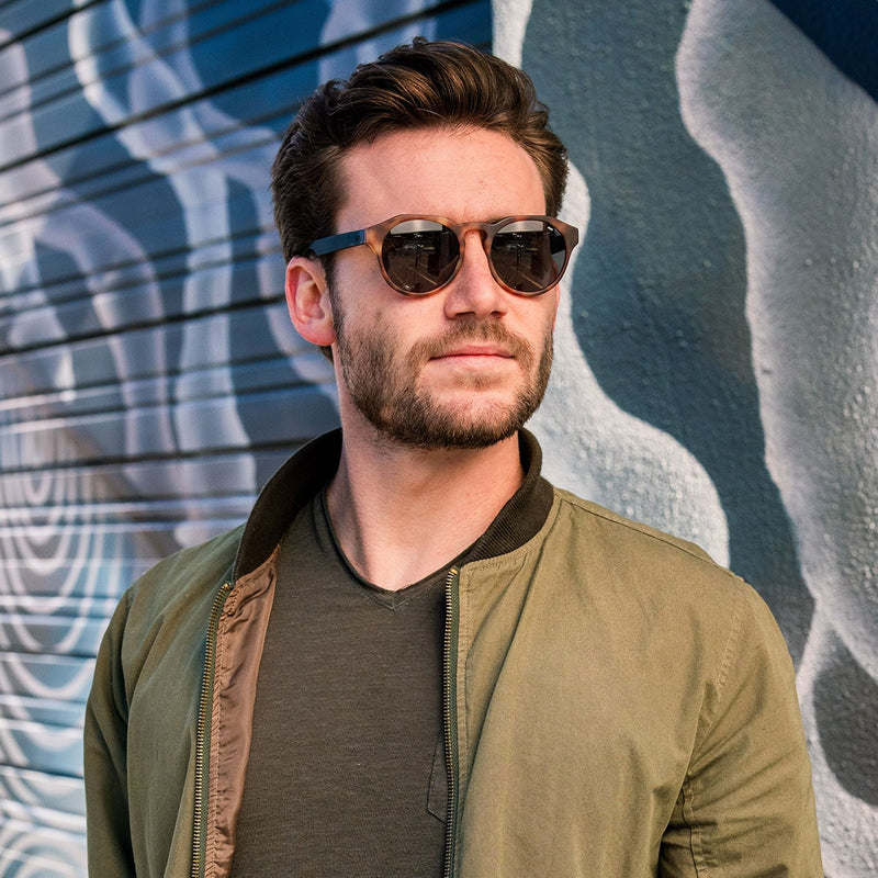 distil cooper sunglasses on bearded man wearing green bomber jacket in alley