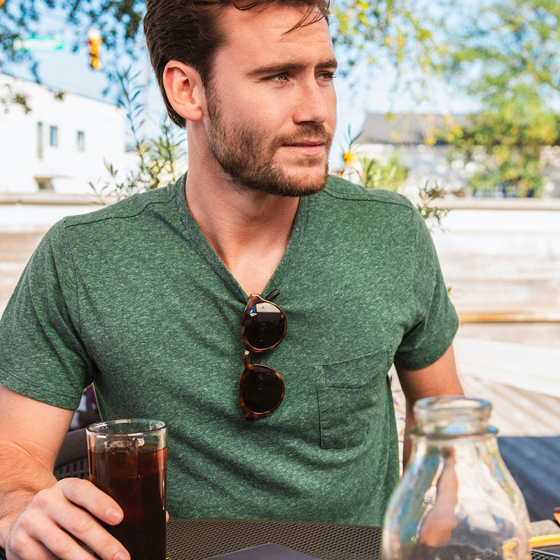 bearded man with distil cooper sunglasses hanging from green tshirt collar
