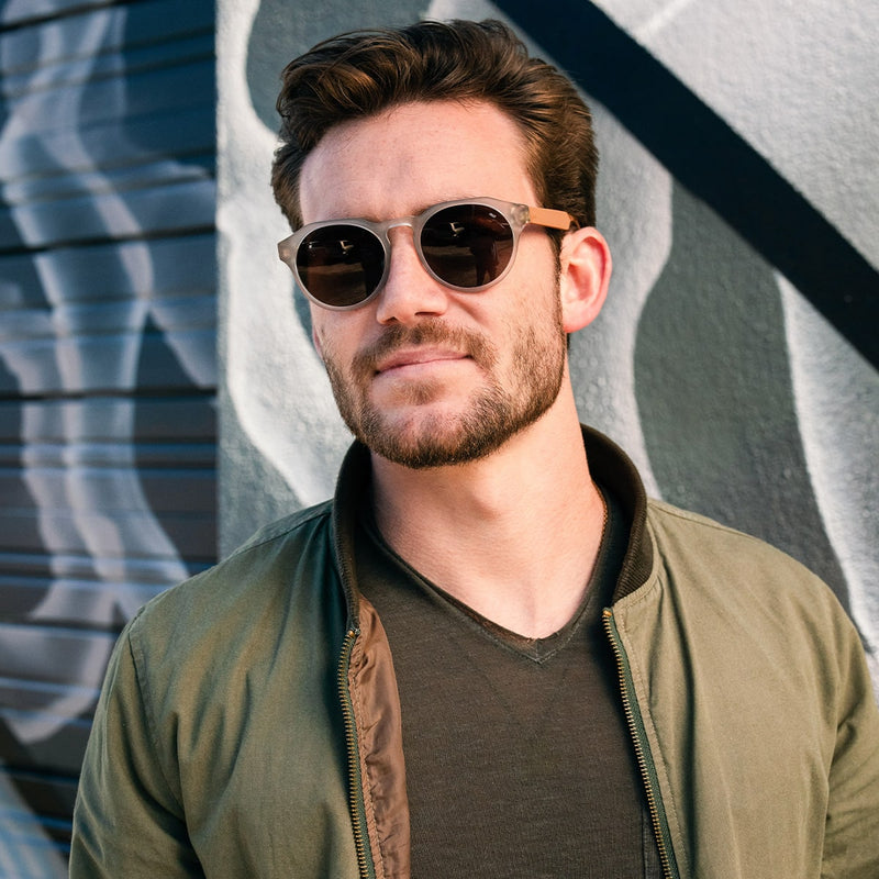 bearded man wearing distil cooper sunglasses with matte crystal frames and amber polarized lens