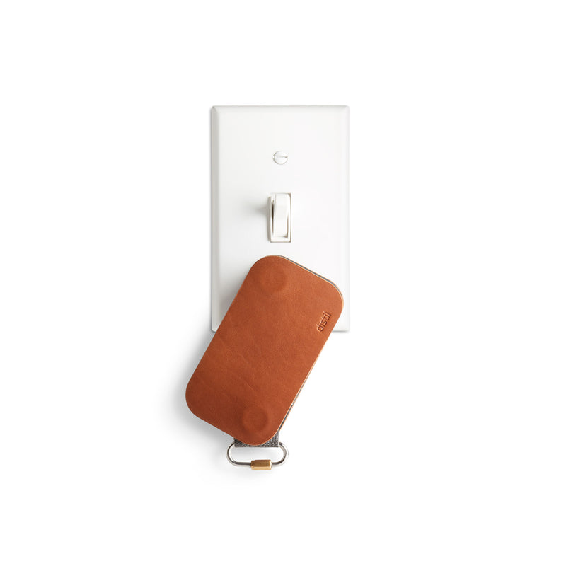 distil brown leather keyfolio hanging from white light switch plate with magnets
