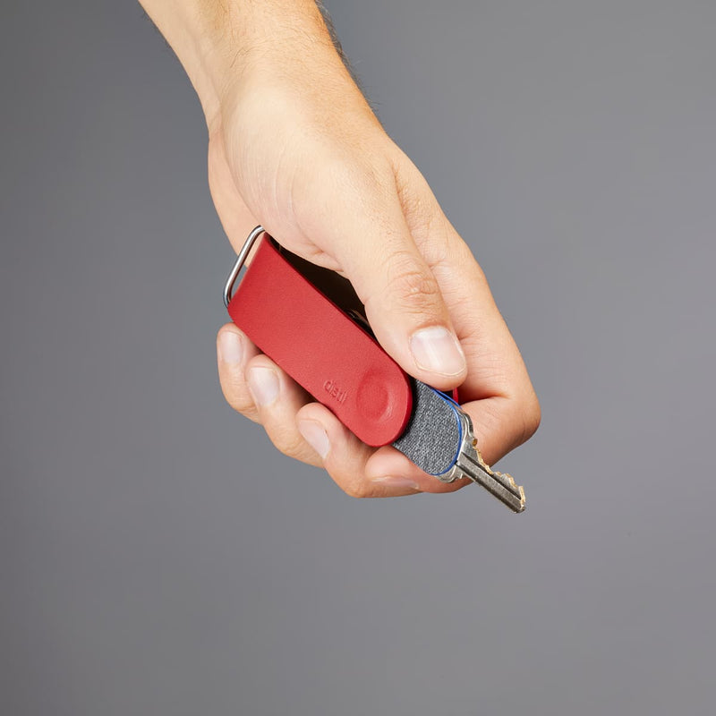 left hand holding distil red leather keyloop with a keymod being used