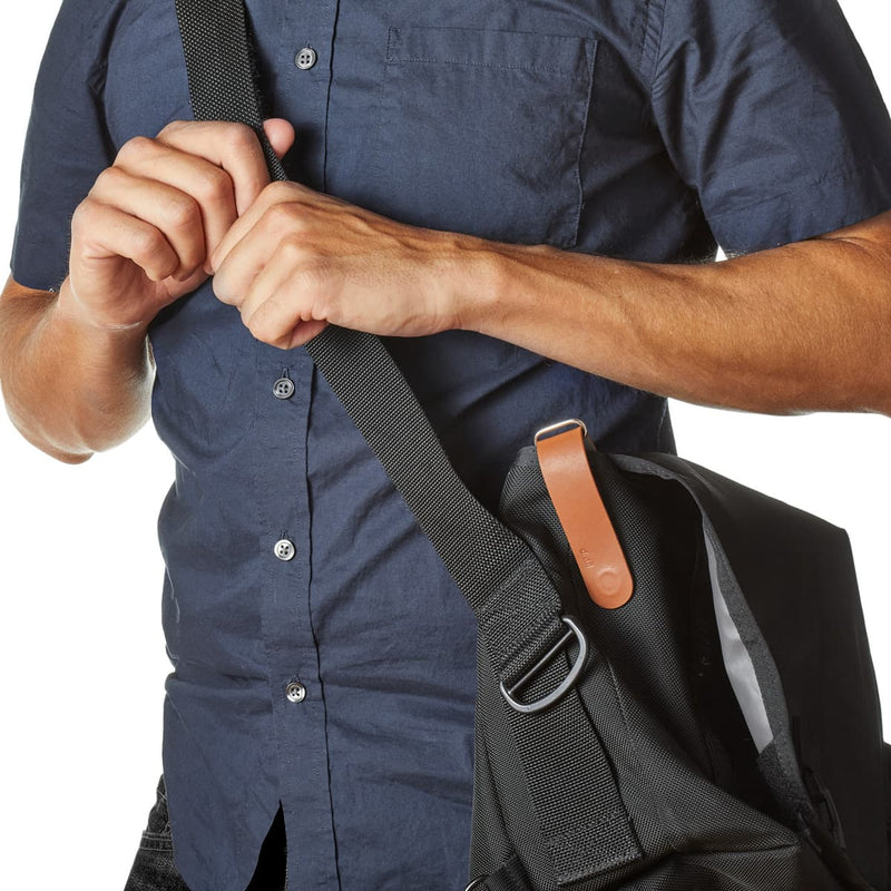man in blue button up shirt carrying black messenger bag with distil brown leather keyloop attached