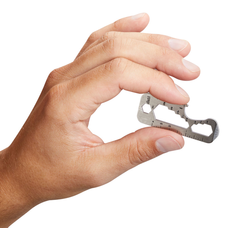 left hand holding distil multitool in between index finger and thumb on white backdrop