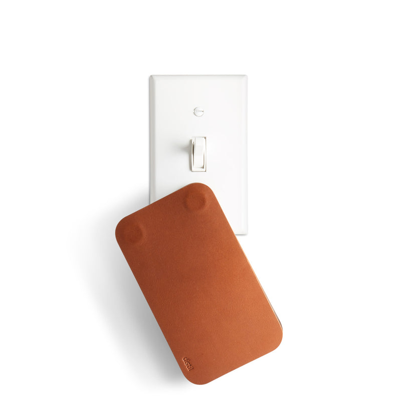 brown leather keyfolio cover hanging from white light switch plate with magnets