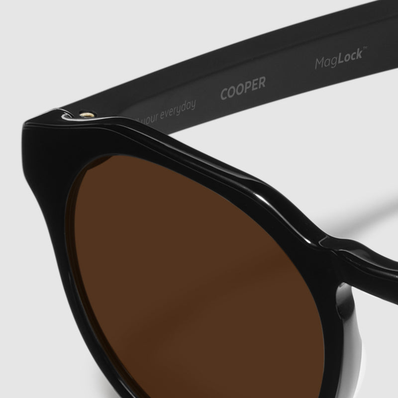 close up view of distil cooper sunglasses with black frames and amber polarized lens