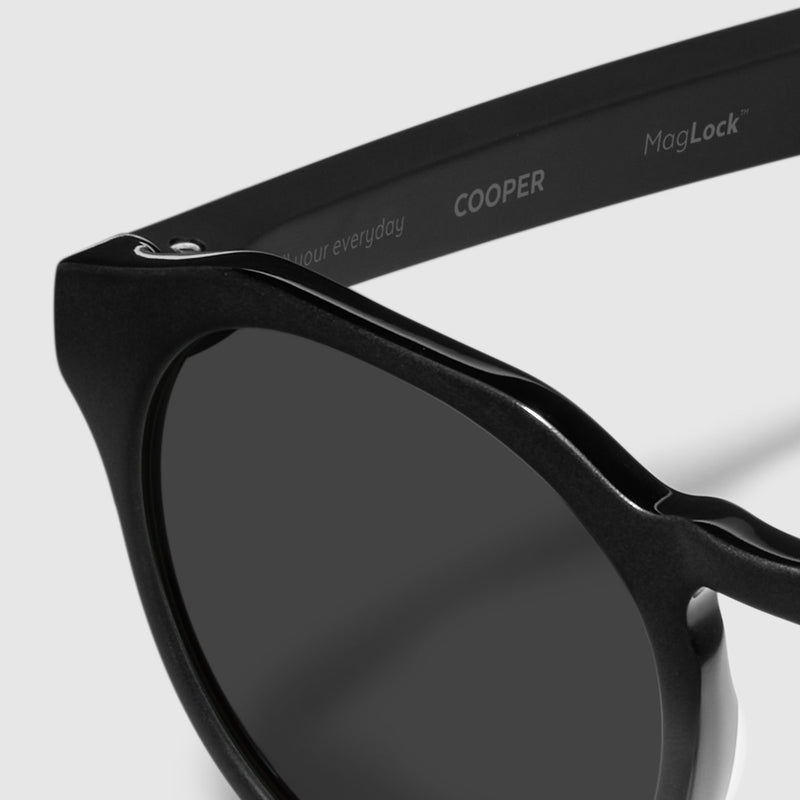 close up view of distil cooper sunglasses with matte black frames and polarized lens