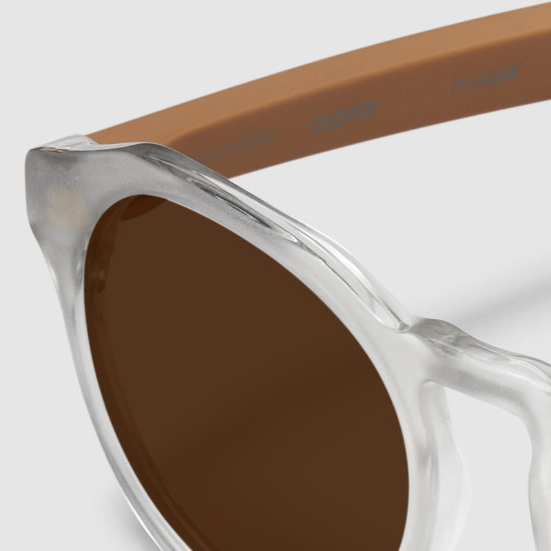 close up view of distil cooper sunglasses with matte crystal frames and amber polarized lens