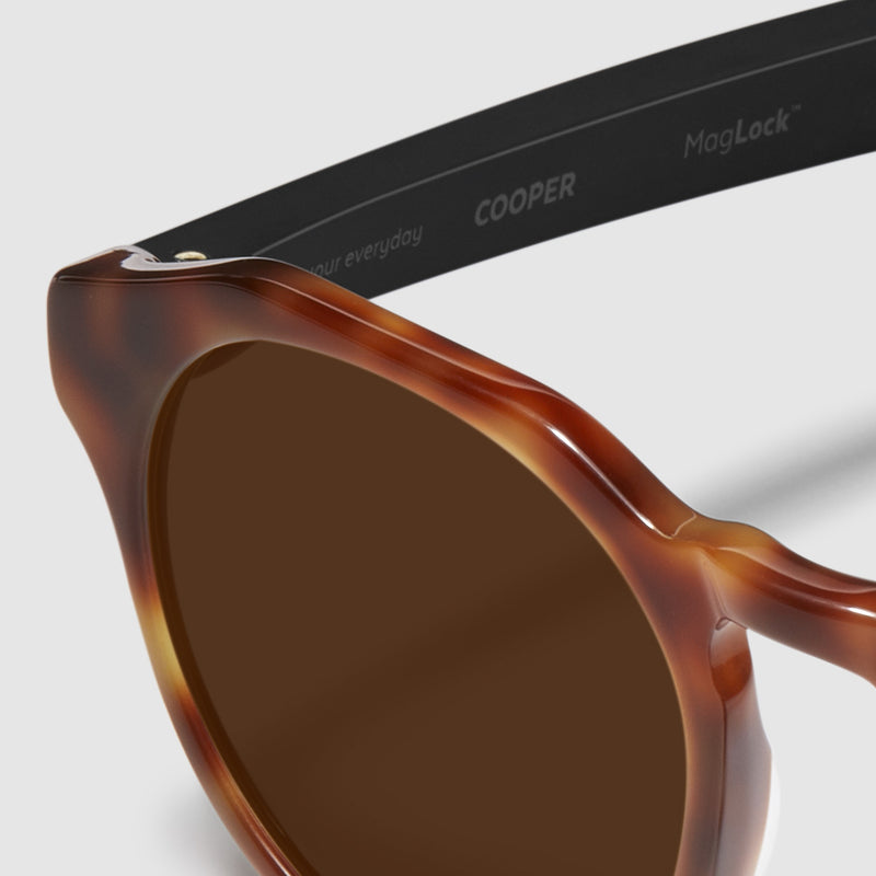 close up view of distil cooper sunglasses with tortoise frames and amber polarized lens